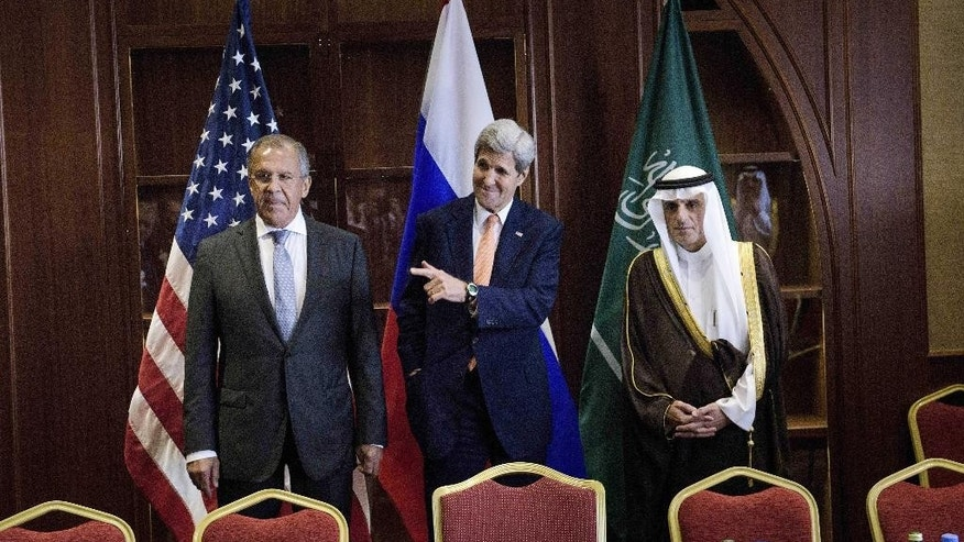 Russia's Foreign Minister Sergey Lavrov, left, U.S. Secretary of State John Kerry, center, and Saudi Foreign Minister Adel al-Jubeir stand together before a trilateral meeting on Monday, Aug. 3, 2015 in Doha. Kerry is meeting his Gulf Arab counterparts for talks in Qatar as he attempts to ease the concerns of key allies over the Iran nuclear deal. (Brendan Smialowski/Pool photo via AP)