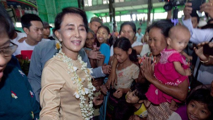 Myanmar opposition leader Aung San Suu Ky is greeted by flood victims upon arrival at an indoor stadium turned into a temporary shelter, in Bago, 80 kilometers (50 miles) northeast of Yangon, Myanmar, Monday, Aug. 3, 2015. A report issued Saturday by the U.N. Office for the Coordination of Humanitarian Affairs cited Myanmar disaster officials estimating that more than 156,000 people had been affected by flooding. (AP Photo/Khin Maung Win)