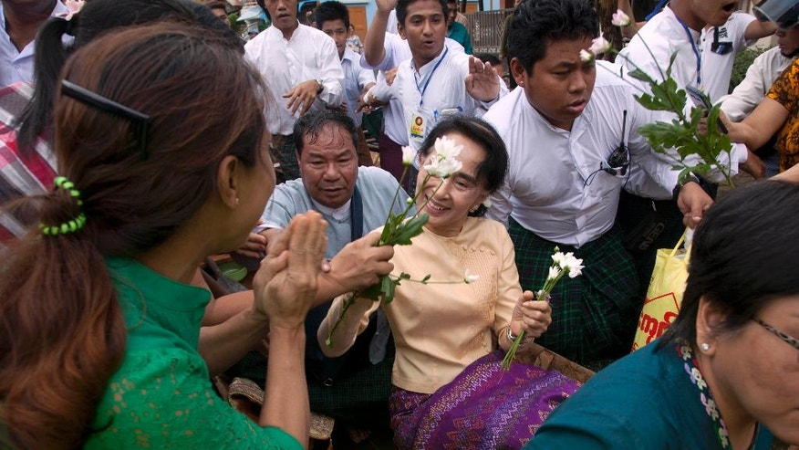 Myanmar opposition leader Aung San Suu Kyi, center, receives flowers on a boat on her way to a monastery where flood victims are sheltered, Monday, Aug. 3, 2015, in Bago, 80 kilometers (50 miles) northeast of Yangon, Myanmar. A report issued Saturday by the U.N. Office for the Coordination of Humanitarian Affairs cited Myanmar disaster officials estimating that more than 156,000 people had been affected by flooding. (AP Photo/Khin Maung Win)