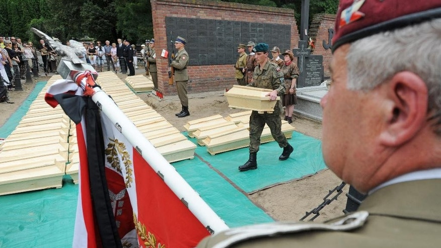 In this Aug. 24, 2012 photo, a soldier carries one of the coffins containing remains of World War II heroes during a ceremony ending archeological works at the Powazki cemetery in Warsaw, Poland. A Polish history institute is seeking to exhume and move the graves of 194 communist-era figures at the Powazki cemetery in order to reach the remains buried below World War II and independence heroes killed on orders from some of those officials.  (AP Photo/Alik Keplicz)
