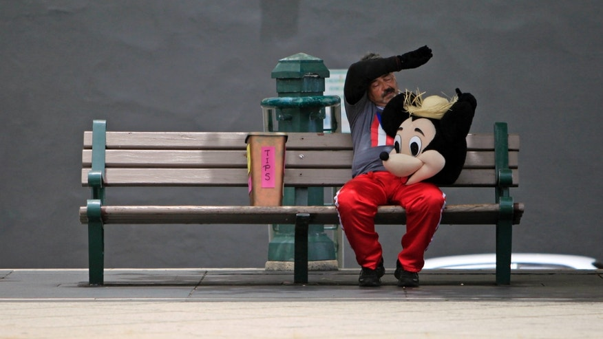 A street performer dressed as Mickey Mouse rests on a bench in Old San Juan, Puerto Rico, on July 1, 2015.