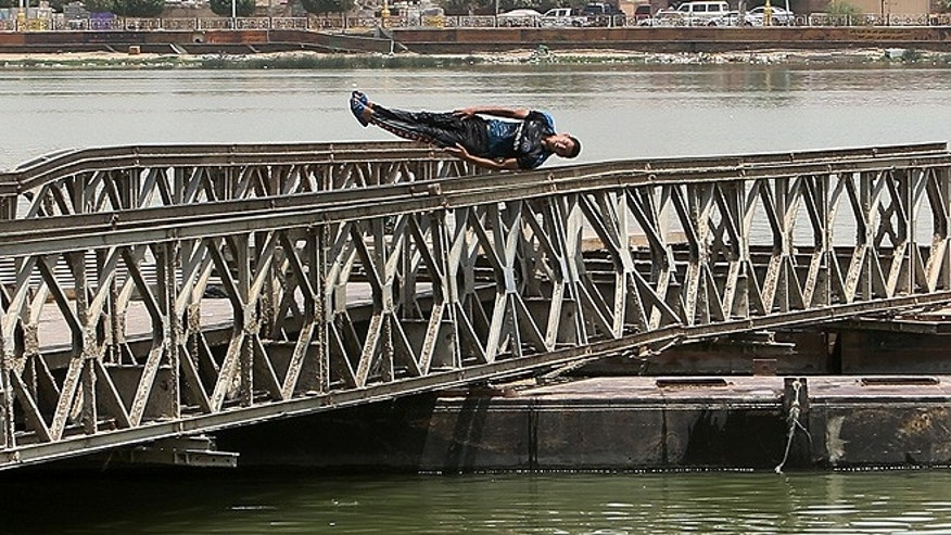 A man dives into the Shat al-Arab river in Basra Iraq. An unprecedented heat wave prompted Iraqi authorities to declare a mandatory four-day holiday beginning Thursday. The government has urged residents to stay out of the sun and drink plenty of water. (AP Photo/ Nabil al-Jurani)