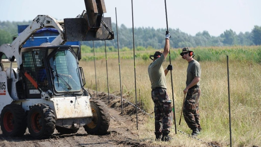 Members of the Hungarian defense force are building a fence at the Hungarian-Serbian border in Asotthalom, 184 km southeast of Budapest, Monday, Aug. 3, 2015. The fence is meant to stop the rising flow of migrants and refugees trying to enter the European Union. (Gergely Zoltan Kelemen/MTI via AP)