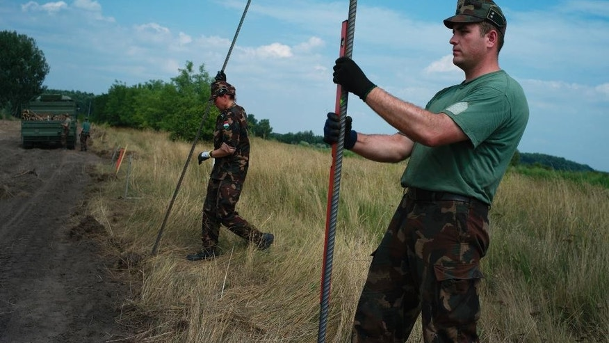 Hungarian soldiers build a fence on the Hungarian - Serbian border near Asotthalom, Hungary on Monday Aug. 3, 2015. Flow of migrants continue to hit Hungary's southern borders while Hungarian soldiers have begun building a 4-meter-high (13-foot-high) fence on the border with Serbia meant to stop the rising flow of migrants trying to enter the European Union. More than 100,000 migrants have reached Hungary on routes across the Balkans so far in 2015. Recently, some 80 percent of them are from war zones like Syria, Iraq and Afghanistan. (AP Photo/Bela Szandelszky)