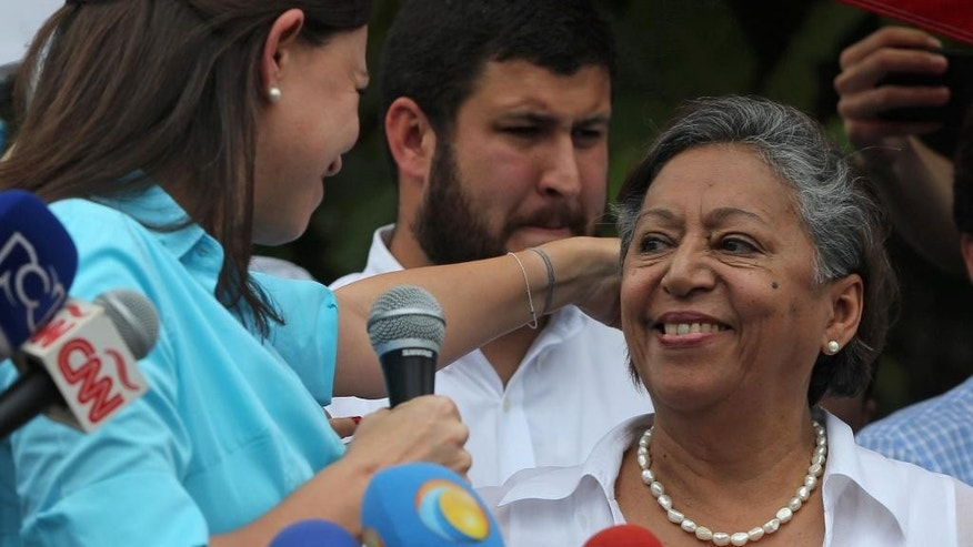 Isabel Pereira, right, stands with opposition leader and former lawmaker Maria Corina Machado as they speak to the media after Machado was unable to register her candidacy for congressional elections, outside the National Electoral Council (CNE) in Los Teques, Venezuela, Monday, Aug. 3, 2015. Pereira, who appears occasionally as a guest political analyst on news programs, registered in Machado's place. Machado is among hardline leaders who called for President Nicolas Maduro to resign last year and helped lead sometimes bloody street protests demanding an end to the South American country's administration. The ruling party stripped her of her congressional seat amid the protests and barred her from holding public office. (AP Photo/Fernando Llano)