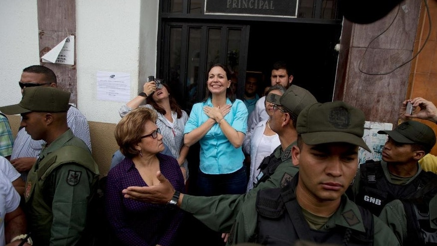 Opposition leader and former lawmaker Maria Corina Machado greets supporters as she leaves the National Electoral Council (CNE) as soldiers stand guard in Los Teques, Venezuela, Monday, Aug. 3, 2015, after she was not allowed to register her candidacy for December's congressional elections. Machado is among hardline leaders who called for President Nicolas Maduro to resign last year and helped lead sometimes bloody street protests demanding an end to the South American country's socialist administration. The ruling party stripped her of her congressional seat amid the protests and barred her from holding public office. (AP Photo/Fernando Llano)