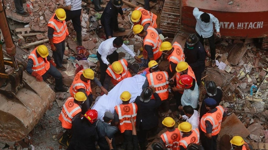 Rescue workers carry the body of a victim at the site of building collapse in Thane, outskirts of Mumbai, India, Tuesday, Aug. 4, 2015. According to an official the building was more than 50 years old and had been damaged by the rain.(AP Photo/Rafiq Maqbool)