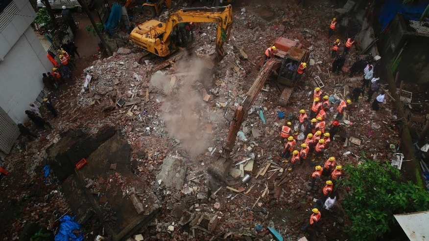 Rescue workers use machinery to clear debris at the site of building collapse in Thane, outskirts of Mumbai, India, Tuesday, Aug. 4, 2015. According to an official the building was more than 50 years old and had been damaged by the rain.(AP Photo/Rafiq Maqbool)