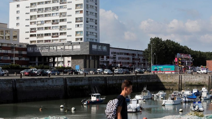 In this Friday, July 31, 2015 photo, a boy walks past the port of Calais, France. Calais, with its huge port bringing visitors across the Channel by ferry, its Eurostar train which stops in nearby Frethun and its highways, is a natural hub for travelers, but they are going somewhere else. (AP Photo/Thibault Camus)
