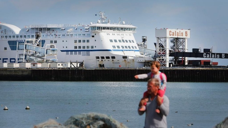 In this Friday, July 31, 2015 photo, a ferry is parked in the port of Calais, France. Calais, with its huge port bringing visitors across the Channel by ferry, its Eurostar train which stops in nearby Frethun and its highways, is a natural hub for travelers, but they are going somewhere else. (AP Photo/Thibault Camus)