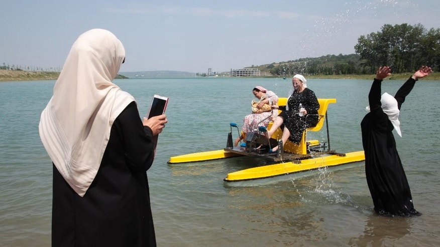 Chechen women enjoy themselves in the water on the outskirts of the regional Chechen capital of Grozny, Russia, Tuesday, Aug. 3, 2015. The beach outside Grozny will be off-limits to men in line with Islamic rules after its inauguration on Tuesday. A separate beach for men is to open later. (AP Photo/ Musa Sadulayev)