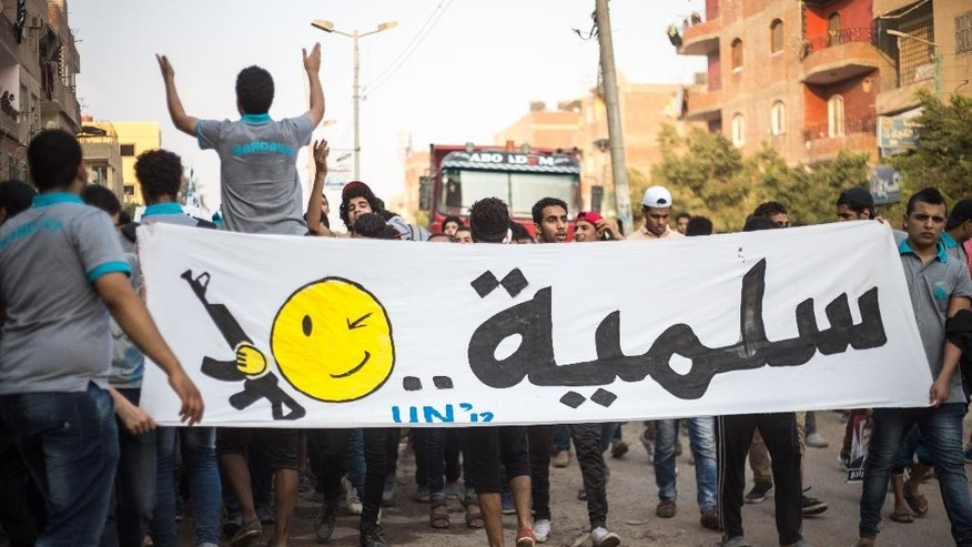 "In this Tuesday, June 23, 2015 photo, members of Ultras Nahdawy, a youth group of the Muslim Brotherhood, carry a banner with an Arabic word meaning ""peaceful"" and a smiley face holding a weapon in a protest ahead of the second anniversary of the ouster of Egyptian President Mohammed Morsi in the Nahia district near Cairo, Egypt. Nahia is a virtual no-go zone for the state at the moment. Hundreds of youth march unopposed in formation down main roads in the district, calling for the ouster of President Abdel-Fattah el-Sissi, the army chief who deposed Morsi before elected to office. (AP Photo/Belal Darder)"