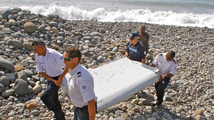 FILE - In this July 29, 2015 file photo, French police officers carry a piece of debris from a plane in Saint-Andre, Reunion Island. If a wing fragment found in the western Indian Ocean turns out to be part of missing Flight 370, experts say, there are probably other pieces of the aircraft that floated off rather than sinking to the bottom of the ocean. Finding them remains the hard part. John Page, an aircraft design expert at the University of New South Wales in Australia, said the discovery of the fragment on Reunion Island leads him to conclude the missing Boeing 777 broke up, most likely when it hit the water nearly 17 months ago. (AP Photo/Lucas Marie, File)