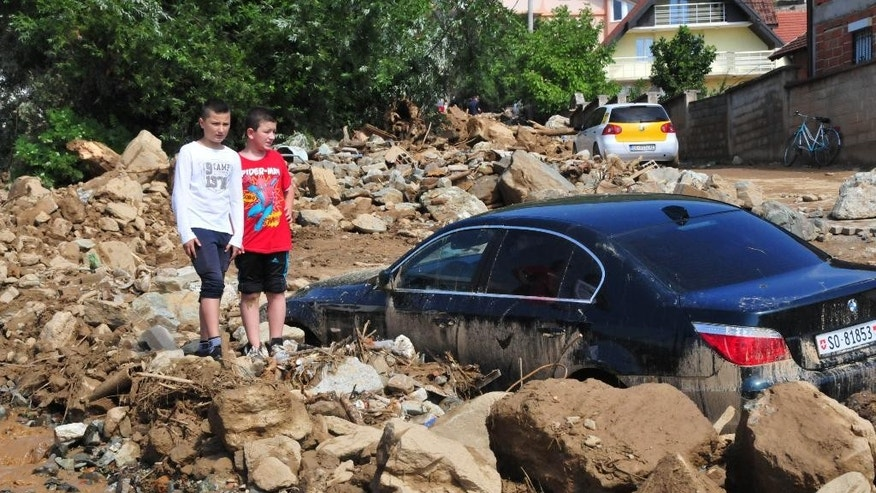 Children look at a destroyed car in a pile of mud, stones and debris after a flood in the village of Golema Recica, just near the town of Tetovo, in northwestern Macedonia, on Tuesday, Aug. 4, 2015. A small number of people including children have died in floods that erupted after an hour of heavy torrential rains and strong winds that hit Tetovo and northwestern region of Macedonia late on Monday.(AP Photo/Zoran Andonov)