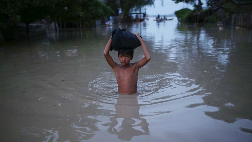In this Aug. 3, 2015, photo, a boy makes his way through floodwaters in Minbu, Magway division, in Myanmar. The Ministry of Social Welfare, Relief and Resettlement said that more than 200,000 people are affected in 11 of the country's 14 states and divisions by flooding. In addition to damage to houses and farmland, infrastructure has been very badly hit, with roads and rail lines cut in many places and telecommunication links broken. (AP Photo/Hkun Lat)