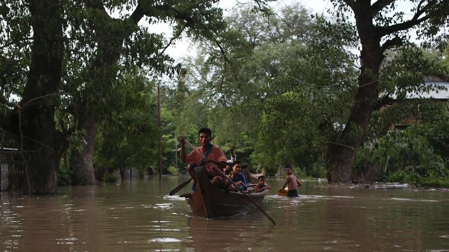 In this Aug. 3, 2015, photo, residents make their way through floodwaters in Minbu, Magway division, in Myanmar. The Ministry of Social Welfare, Relief and Resettlement said that more than 200,000 people are affected in 11 of the country's 14 states and divisions by flooding. In addition to damage to houses and farmland, infrastructure has been very badly hit, with roads and rail lines cut in many places and telecommunication links broken. (AP Photo/Hkun Lat)