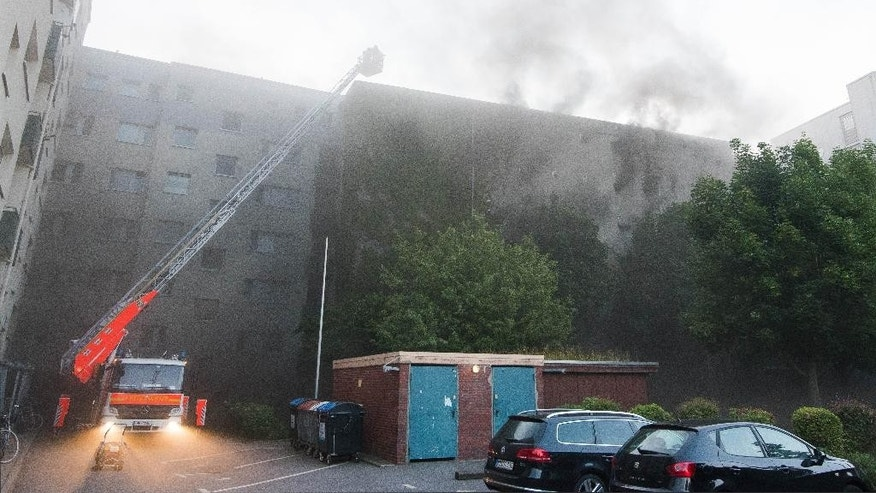 Smoke rises from a burning former air-raid shelter in Hamburg, northern Germany, Tuesday, Aug. 4, 2015. Authorities say 27 people have been injured in the fire and subsequent explosion. (Daniel Bockwoldt/dpa via AP)