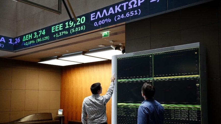 Two men check an index board at the reception hall of the Athens' Stock Exchange, in Athens, Greece, Tuesday, Aug. 4, 2015. The Stock Exchange is suffering a second day of losses after reopening amid capital controls, with banks again suffering the worst damage. (AP Photo/Yorgos Karahalis)