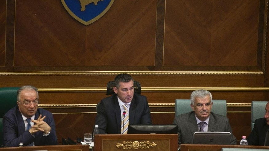 Speaker of the parliament Kadri Veseli, center, addresses Kosovo lawmakers during a debate passing constitutional amendments that would allow the establishment of a special court to prosecute its top leaders and former guerrilla fighters for war crimes in capital Pristina on Monday, Aug. 3, 2015. Kosovo's Parliament on Monday approved a constitutional amendment to set up a special court to prosecute former leaders over war crimes, including the killing of hundreds of Serb civilians. (AP Photo/Visar Kryeziu)