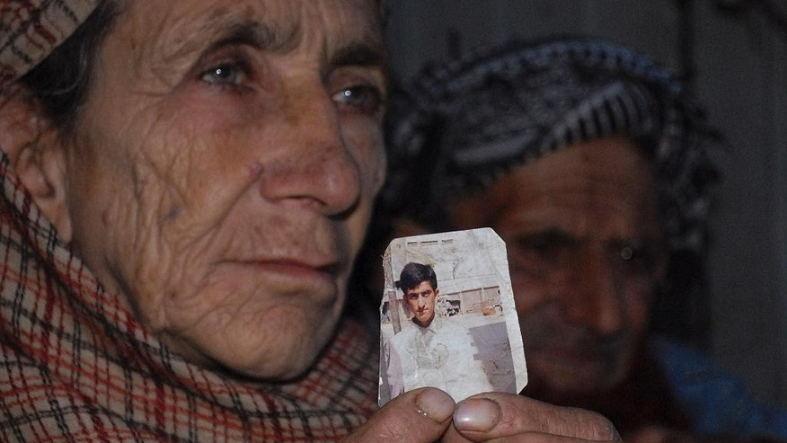 FILE - In this March 14, 2015, file photo, Makhni Begum holds a photograph of her son Shafqat Hussain in Muzaffarabad, Pakistan. A Pakistani jail official says Hussain, convicted of killing a boy in 2004 and spared of execution four times earlier, has been hanged in Karachi prison. (AP Photo/M.D. Mughal, File)