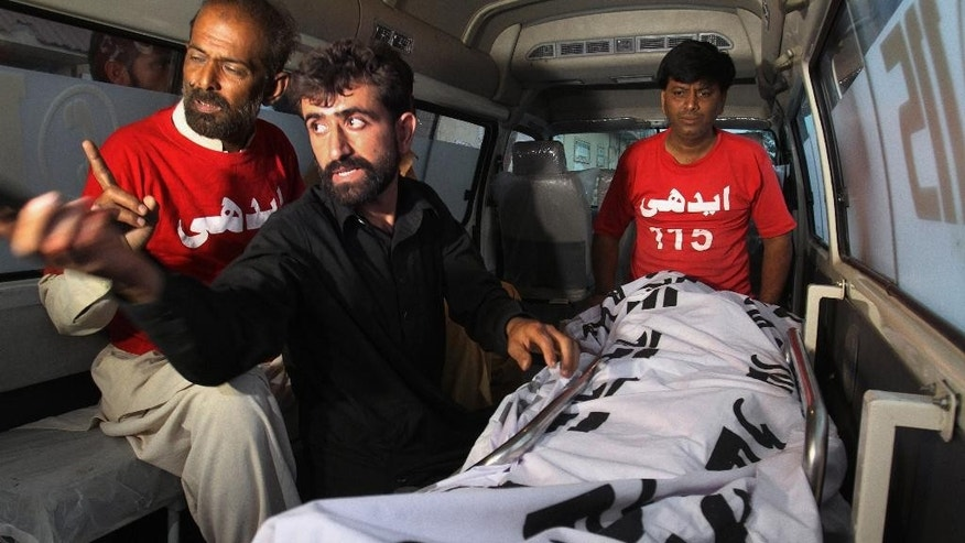Pakistani Kashmiri Abdul Majeed, center, sits in front of the lifeless body of his brother Shafqat Hussain, who was convicted of killing a 7-year-old boy, following his execution in Karachi, Pakistan, Tuesday, Aug. 4, 2015. Pakistan has executed Tuesday Hussain, convicted of killing a 7-year-old boy in 2004, his family and lawyers said when he himself was 14 years old, officials at Karachi prison said. (AP Photo/Fareed Khan)