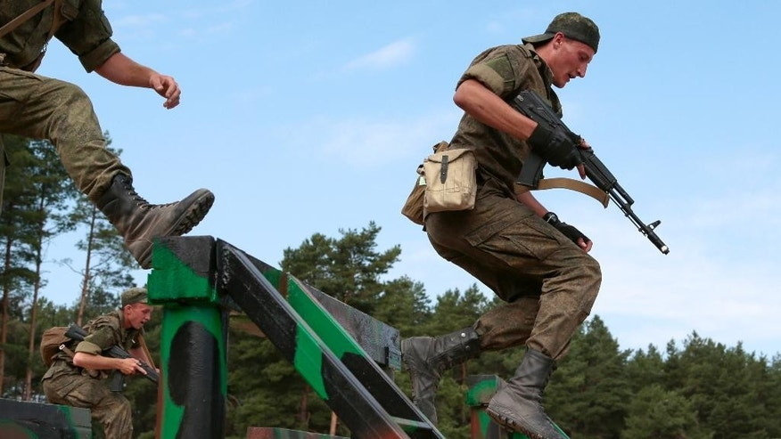 "Russian paratroopers overcome obstacles during the ""Paratrooper's platoon"" military game at a Dubrovichi shooting range outside of Ryazan, some 170 kms south east of Moscow, Russia, Tuesday, Aug. 4, 2015. The competitions called the International Army Games involve troops from Russia and several other nations.  (AP Photo/Ivan Sekretarev)"