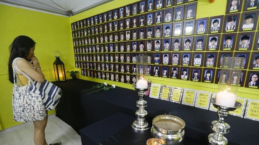 A woman prays in front of portraits of the victims aboard the sunken ferry Sewol in the water off the southern coast, in Seoul, South Korea, Tuesday, Aug. 4, 2015. South Korea said Tuesday that it had agreed to a 85.1 billion won ($73 million) deal with a Chinese-led consortium to salvage a ferry that sunk in an accident that killed more than 300 people in April last year. The formal contract could be signed as early as Wednesday. (AP Photo/Ahn Young-joon)