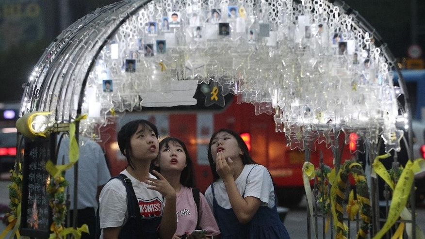 High school students watch portraits of victims aboard the sunken ferry Sewol in the water off the southern coast, in Seoul, South Korea, Tuesday, Aug. 4, 2015. South Korea said Tuesday that it had agreed to a 85.1 billion won ($73 million) deal with a Chinese-led consortium to salvage a ferry that sunk in an accident that killed more than 300 people in April last year. The formal contract could be signed as early as Wednesday. (AP Photo/Ahn Young-joon)