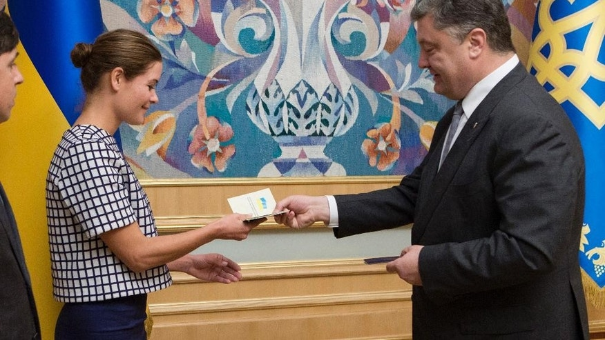 Maria Gaidar, the daughter of Russia's 1990s reformist prime minister Yegor Gaidar, receives a Ukrainian passport from Ukraine's President Petro Poroshenko, right, in Kiev, Ukraine, Tuesday, Aug. 4, 2015. Gaidar's appointment as deputy governor of Odessa, now led by former Georgian President Mikhail Saakashvili, has been painted as a betrayal in Russia. (AP Photo/Mykhailo Markiv, Pool)