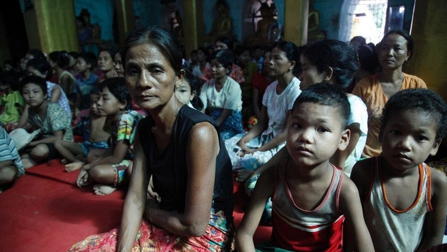 Flood victims gather inside a monastery, opened as a temporary relief camp, in Myauk U, Rakhine State, western Myanmar, Tuesday, Aug 4, 2015. New devastation is feared in Myanmar as water from the badly flooded central and northern regions flows down rivers to the country's more populous areas. Officials say the death toll from weeks of almost continuous rain is 46, with more than 200,000 people affected by flooding in 11 of the country's 14 states and divisions.  (AP Photo/Khin Maung Win)