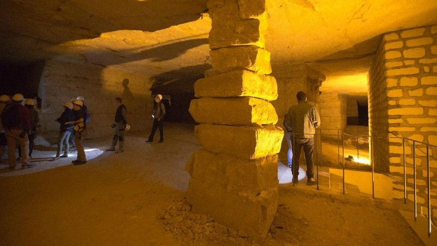 Visitors tour the depths of the Vincennes quarry during a press visit, near Paris, France, Wednesday Aug. 5, 2015.  The tunnels zigzagging through limestone were created to provide building materials for Paris. Then they became the damp home to vast subterranean mushroom farms. Now, deep beneath the city's largest park, the quarry is usually off-limits, deemed too dangerous for regular visitors. Unescorted spelunkers face a 60-euro ($65) fine, but on Wednesday the 20-meter (66-foot) spiral staircase leading down into the earth from the Bois de Vincennes park was briefly opened to journalists. (AP Photo/Jacques Brinon)