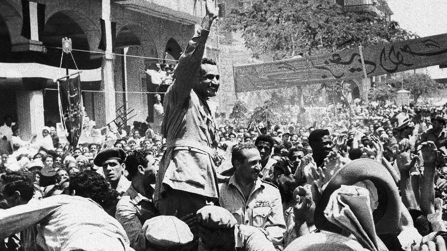 FILE - In this June 18, 1956 file photo, Egyptian President Gamal Abdel Nasser waves in response to cheering supporters as he moves through Port Said to raise the Egyptian flag over the Navy House. Flag-raising was part of ceremony in which Egypt formally took over guardianship of the Suez Canal Zone after British occupation of more than 70 years. (AP Photo, File)