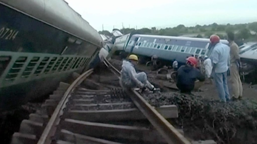 In this image made from video, people gather by the twisted track alongside two derailed trains in Harda in Madhya Pradesh state, India, Wednesday, Aug. 5, 2015. Two passenger trains derailed over a bridge in central India while crossing a track that was flooded by heavy monsoon rains, killing at a number of people, officials said Wednesday.(Photo via AP Video)