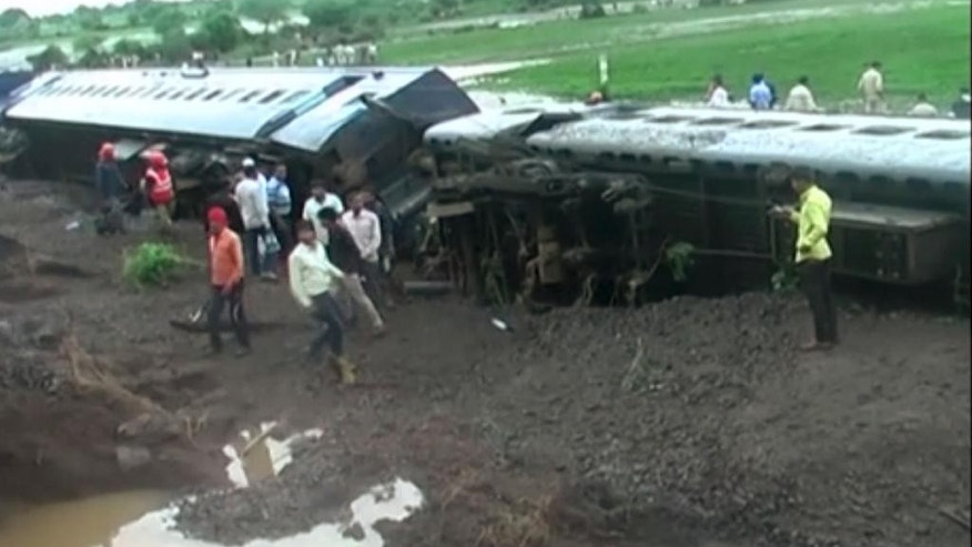 In this image made from video, people gather by the scene where two trains derailed in Harda in Madhya Pradesh state, India, Wednesday, Aug. 5, 2015. Two passenger trains derailed over a bridge in central India while crossing a track that was flooded by heavy monsoon rains, killing at a number of people, officials said Wednesday. (Photo via AP Video)