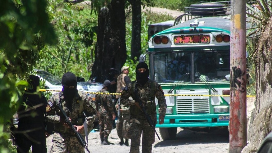 Soldiers guard the scene after a passenger bus was attacked in San Pedro Perulapan, El Salvador, Wednesday, Aug. 5, 2015. Gunmen boarded the bus near the Salvadoran capital and opened fire, killing four people and wounding several others a week after a string of bus attacks brought service to a halt. (AP Photo/Salvador Melendez)