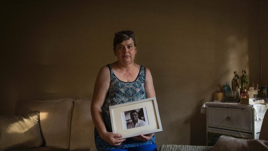 Jacquita Gomes, 53, holds a portrait of her husband, Patrick Gomes, 56, the in-flight supervisor on the ill fated flight MH370, in their home outside Kuala Lumpur, Malaysia on Wednesday, Aug. 5, 2015. (AP Photo/Joshua Paul)