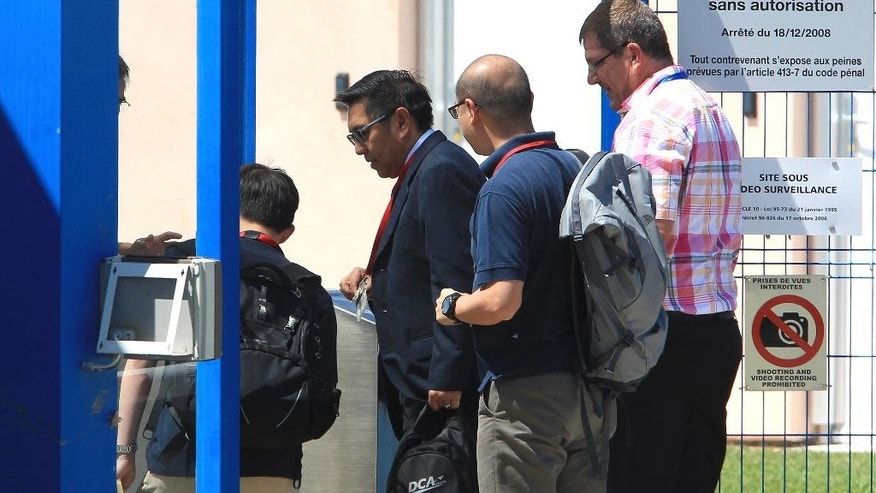 Malaysia's Department of Civil Aviation Director General Azharuddin Abdul Rahman, second left, arrives at the Direction Generale de l'Armement (DGA) facilities in Balma, near Toulouse, south-western France, Wednesday, Aug. 5, 2015 to start to examine an airplane wing fragment that many people believe could offer the first tangible clue into the fate of the missing Malaysia Airlines Flight 370. Malaysia Airlines Flight 370 vanished in March 2014 while flying from Kuala Lumpur to Beijing with 239 people aboard. (AP Photo/Bob Edme)