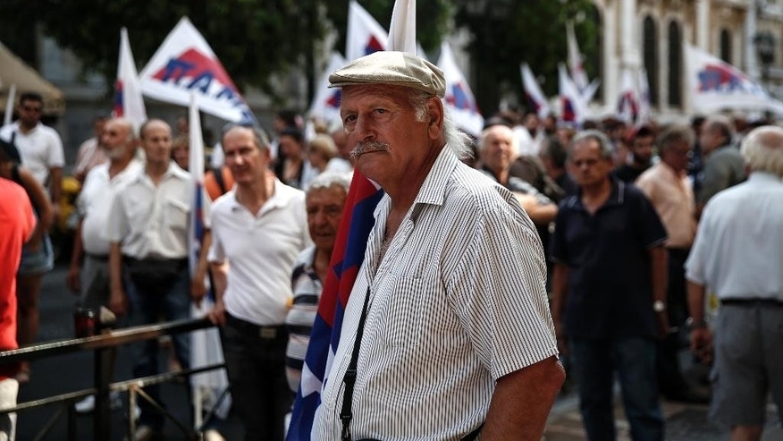 Supporters of the Communist-affiliated PAME labor union take part in an anti-austerity rally outside the Labor Ministry in Athens, Greece, on Wednesday, Aug. 5, 2015. Greece's economy is reeling from the impact of limits on money withdrawals and transfers that the government imposed on June 29 to avoid a collapse of the banking sector. Uncertainty over Greece's negotiations for a new bailout and over the stability of the government have heightened concerns. (AP Photo/Yorgos Karahalis)