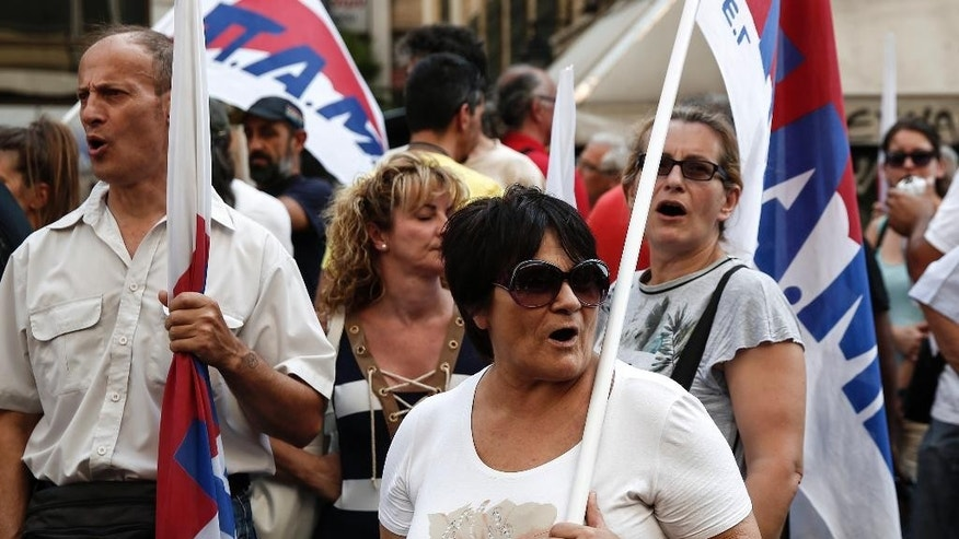 Supporters of the Communist-affiliated PAME labor union shout slogans during an anti-austerity rally outside the Labor Ministry in Athens, Greece, on Wednesday, Aug. 5, 2015. Greece's economy is reeling from the impact of limits on money withdrawals and transfers that the government imposed on June 29 to avoid a collapse of the banking sector. Uncertainty over Greece's negotiations for a new bailout and over the stability of the government have heightened concerns.  (AP Photo/Yorgos Karahalis)