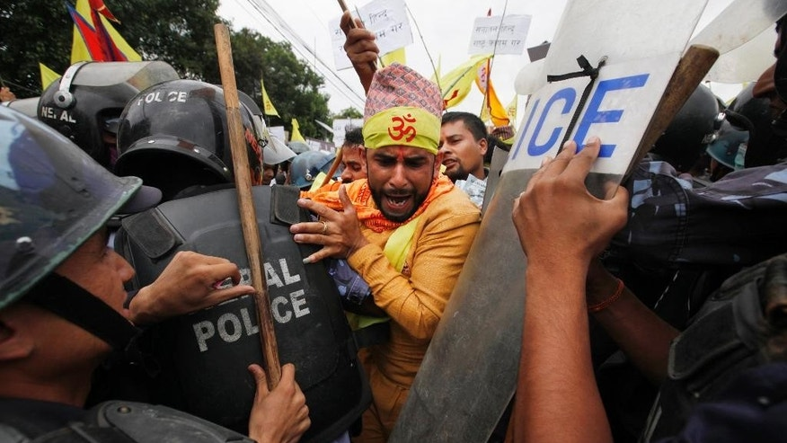 Nepalese police stop Hindu activists as they try to enter a restricted area near the Nepalese Constituent Assembly Hall during a protest in Kathmandu, Nepal, Wednesday, Aug. 5, 2015. About 500 protesters demanding Nepal be declared a Hindu state in the new constitution clashed with police. No one was injured in scuffles and there were no arrests. (AP Photo/Niranjan Shrestha)