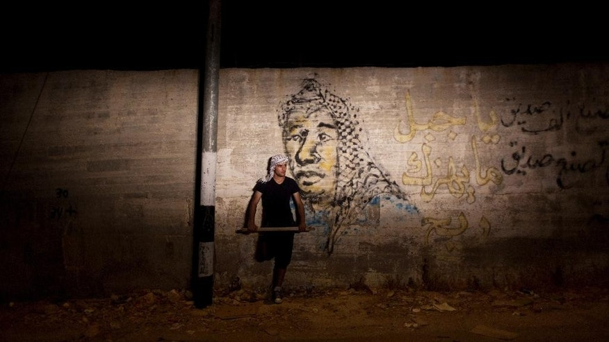 "In this Tuesday, Aug. 4, 2015 photo, a Palestinian villager stands guard in front of graffiti depicting late Yasser Arafat and Arabic that reads ""the mountain is not shaken by the wind,"" at the entrance of the West Bank village of al-Jab'a, near Bethlehem. The Residents of the village formed groups of defense volunteers to guard themselves from attacks of Israeli settlers. While the village's mosque was vandalized and torched by Israeli extremists earlier this year, tensions rose higher this week after suspected Jewish assailants set fire to a West Bank home and burned a sleeping Palestinian toddler to death and left his family seriously wounded. (AP Photo/Nasser Nasser)"