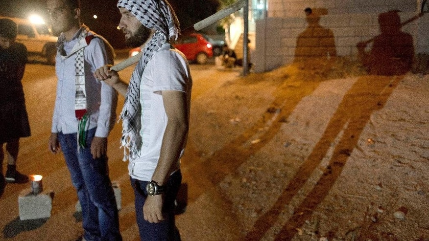 In this Tuesday, Aug. 4, 2015 photo, Palestinian villagers stand guard at the entrance of the West Bank village of al-Jab'a, near Bethlehem. The Residents of the village formed groups of defense volunteers to guard themselves from attacks of Israeli settlers. While the village's mosque was vandalized and torched by Israeli extremists earlier this year, tensions rose higher this week after suspected Jewish assailants set fire to a West Bank home and burned a sleeping Palestinian toddler to death and left his family seriously wounded. (AP Photo/Nasser Nasser)