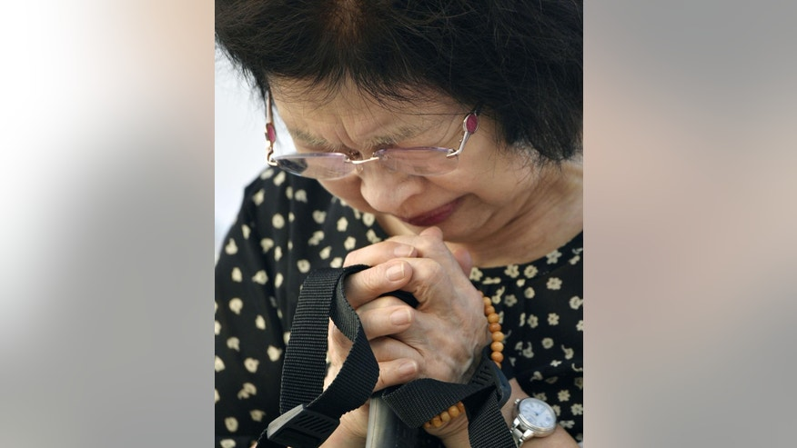 A woman prays for the victims of the atomic bombing at the Hiroshima Peace Memorial Park in Hiroshima, western Japan early Thursday, Aug. 6, 2015. Japan marked the 70th anniversary of the atomic bombing of Hiroshima. (Kyodo Photo via AP) JAPAN OUT, MANDATORY CREDIT