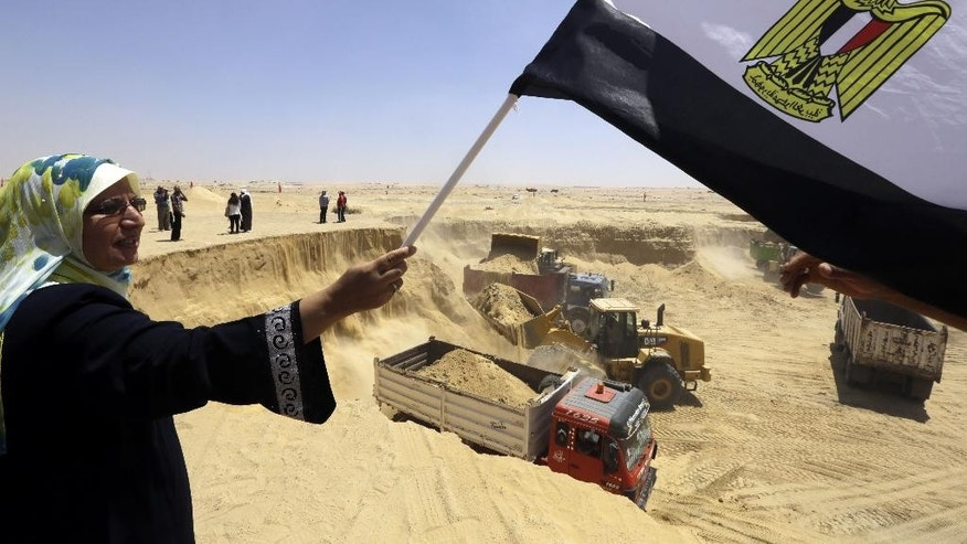FILE - In this Aug. 12, 2014, file photo, an Egyptian woman waves a national flag as laborers work on the Suez Canal during a media tour, in Ismailia, Egypt. Egypt's Suez Canal officially opens a new, parallel waterway on Thursday, Aug. 6, 2015, to allow two-way traffic to cross with virtually no waiting. (AP Photo/Amr Nabil, File)
