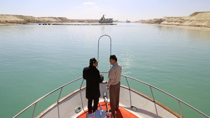 FILE - In this Feb. 22, 2015 file photo released by the Egyptian Presidency, President Abdel-Fattah el-Sissi, left, speaks with an official during his visit to the Suez Canal in Ismailia, Egypt. Egypt's Suez Canal officially opens a new, parallel waterway on Thursday, Aug. 6, to allow two-way traffic to cross with virtually no waiting.  (Egyptian Presidency via AP, File)