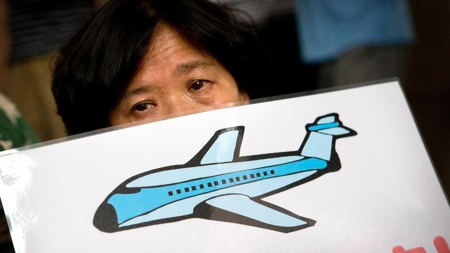 Bao Lanfang, right, whose daughter-in-law, son, and granddaughter were aboard Malaysia Airlines Flight 370, cries while demonstrating outside the company's offices in Beijing, Thursday, Aug. 6, 2015. Families aching for closure after their relatives disappeared aboard Malaysia Airlines Flight 370 last year vented deep frustration Thursday at conflicting signals from Malaysia and France over whether the finding of a plane part had been confirmed. (AP Photo/Mark Schiefelbein)