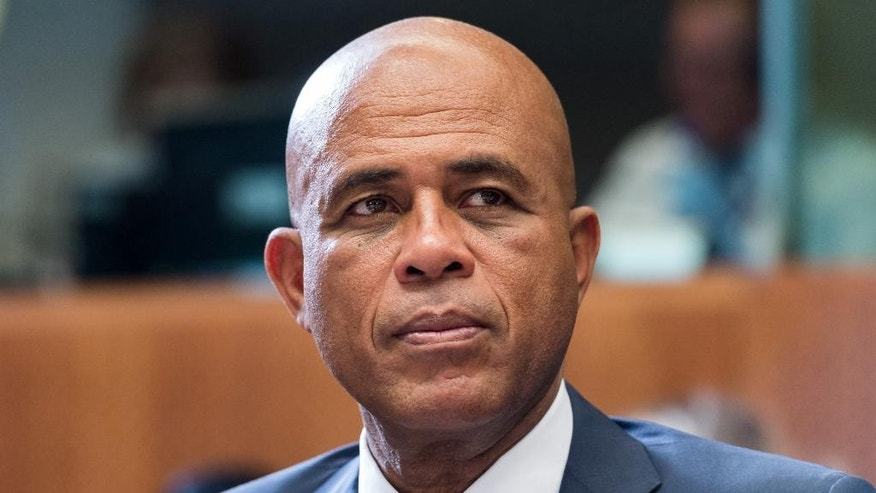 """FILE - In this June 10, 2015 file photo, Haiti's President Michel Joseph Martelly waits for the start of a round table meeting at the EU-CELAC summit in Brussels. Hostile comments made by Martelly to a woman at a campaign rally in Haiti have prompted a party in his coalition to remove three officials from his government. Martelly was at a rally in late July 2015 when a woman complained that his government failed to bring electricity to her community. Haitian media reported that he told her in Haitian Creole to """"go get a man and go in the bushes"""" to have sex. (AP Photo/Geert Vanden Wijngaert, File)"""