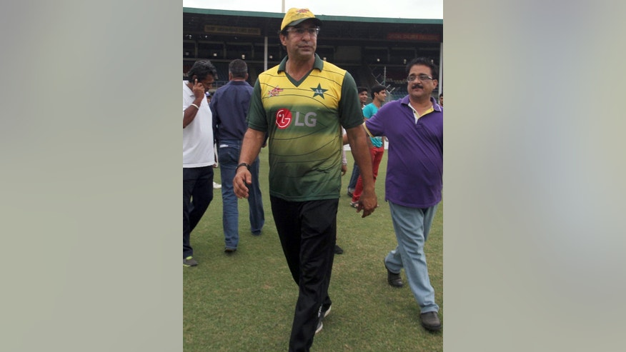 Pakistan's former cricket captain Wasim Akram leaves after talking to media regarding a gun attack at the National Stadium in Karachi, Pakistan, Wednesday, Aug. 5, 2015. A gunman opened fire on Pakistan's legendary former cricket captain Wasim Akram in an apparent incident of road-rage in the southern city of Karachi on Wednesday, police said.   (AP Photo/Fareed Khan)