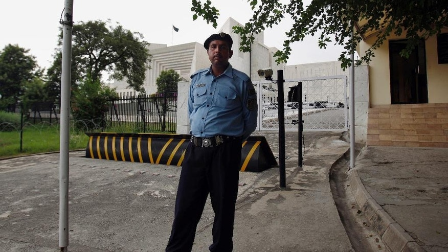 A police officer stands guard in front of the Supreme Court building in Islamabad, Pakistan, Wednesday, Aug. 5, 2015. Pakistan's Supreme Court ruled on Wednesday to allow military trials for terror suspects _ the latest in the government's intensified campaign against terrorism in the wake of last year's Taliban attack on a school that killed nearly 150 people, almost all of them children. (AP Photo/Anjum Naveed)