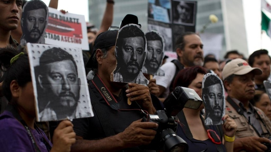 Journalists and activists hold up cut-out images of slain photojournalist Ruben Espinosa during a protest at MexicoCity's Angel of the Independence monument, Sunday, Aug. 2, 2015. Mexico City officials said Sunday they are pursuing all lines of investigation into the killing Espinosa and four other women whose bodies were found in the capital, where he had fled from the state of Veracruz because of harassment. According to the Committee to Protect Journalists, 11 journalists have been killed there since 2010, all during the administration of Gov. Javier Duarte. (AP Photo/Dario Lopez-Mills)